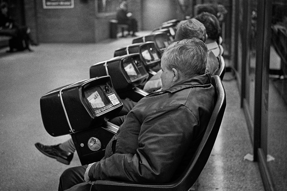 Voyageurs regardant la télé dans un terminus